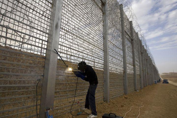 Un ouvrier israélien travaille à la construction de la frontière électrifiée entre Israël et le Sinaï égyptien, le 15 février 2012. (AHMAD GHARABLI / AFP)