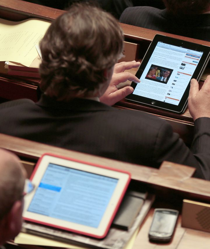 Un député lit la presse en ligne sur sa tablette lors d'une séance de questions au gouvernement, le 10 octobre 2012, à Paris. (JACQUES DEMARTHON / AFP)