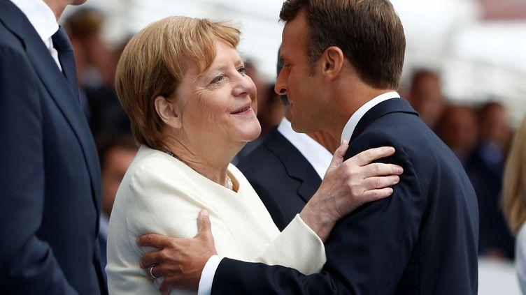 La chancelière allemande Angela Merkel et Emmanuel Macron, dimanche 14 juillet 2019 à Paris. (Kamil Zihnioglu / REUTERS)