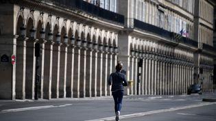 Une femme faisant son footing dans les rues de Paris pendant le confinement. (FRANCK FIFE / AFP)