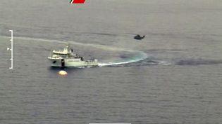 Des bateaux et un hélicoptère des gardes-côtes italiens cherchant des survivants du naufrage d'un chalutier remplis de centaines de migrants, le 19 avril 2015 au large des côtés italiennes. (GUARDIA COSTIERA / AFP)