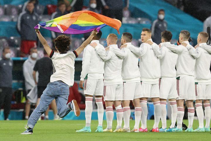 Un militant brandit un drapeau arc-en-ciel au moment des hymnes avant le match Allemagne-Hongrie à Munich (Allemagne) le 23 juin 2021. (ALEXANDER HASSENSTEIN / POOL / AFP)