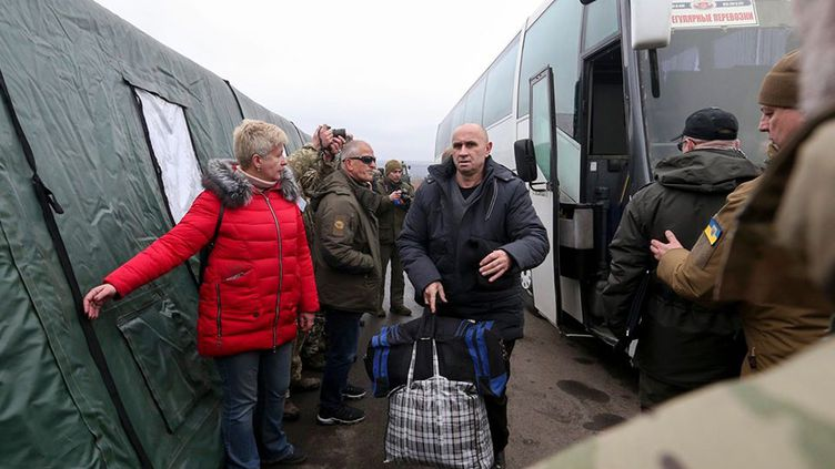 Des Ukrainiens sortent d'un bus lors d'un échange de prisonniers entre l'Ukraine et les séparatistes pro-russes près du poste de contrôle de Mayorsk, le 29 décembre 2019. (HO / UKRAINIAN PRESIDENTIAL PRESS SERVICE / AFP)