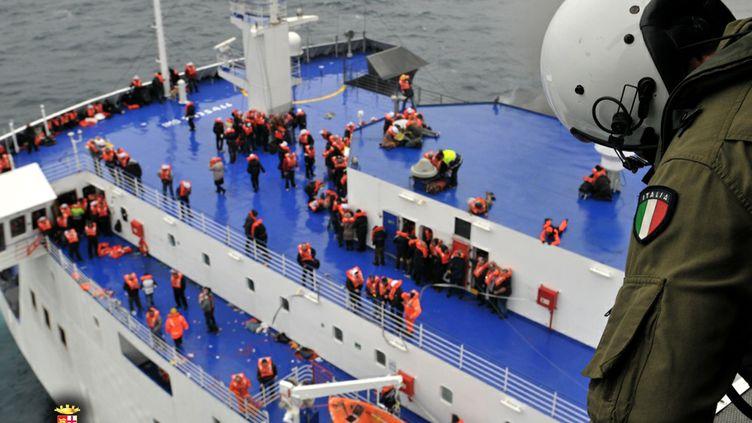 Des passagers du ferry battant pavillon italien, frappé dimanche 28 décembre 2014 par un incendie au large des côtes de l'Albanie, en cours d'évacuation. (MARINA MILITARE / AFP)