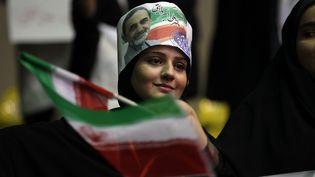 Une femme arbore les couleurs du candidat conservateur Ali Akbar Velayati lors d'un meeting, le 12 janvier 2013, à Téhéran (Iran). (ATTA KENARE / AFP)