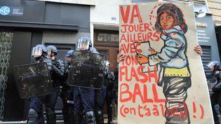 """""""Va jouer ailleurs avec ton flash ball, on t'a à l'oeil"""", panneau tenu par un manifestant entouré de CRS, le 8 novembre 2014, à Paris. (NATHANAEL CHARBONNIER / FRANCE-INFO)"""