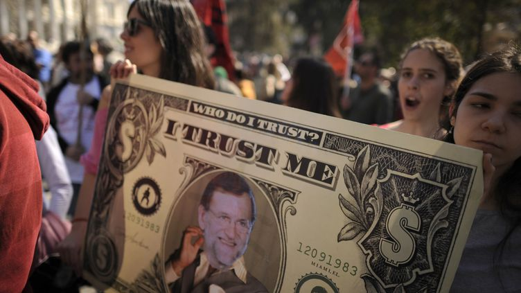 Des manifestants anti-austérité brandissent un billet de un dollar à l'effigie de Mariano Rajoy, le Premier ministre espagnol, à Madrid, le 11 mars 2012. (PEDRO ARMESTRE / AFP)
