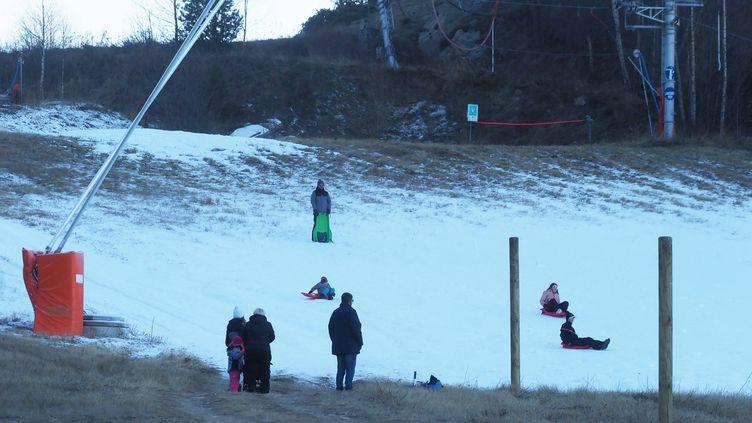 Des enfantsfont de la luge malgré le manque de neige, le 3 janvier 2019, dans la station de ski du Cambre d'Aze (Pyrénées-Orientales). (RAYMOND ROIG / AFP)
