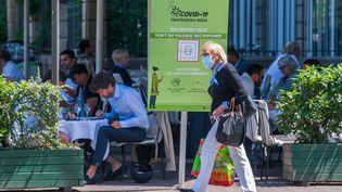 Une femme masquée passe devant une terrasse de restaurant et un panneau de prévention sanitaire, le 2 juin 2020, à Strasbourg (Bas-Rhin). (PATRICK HERTZOG / AFP)