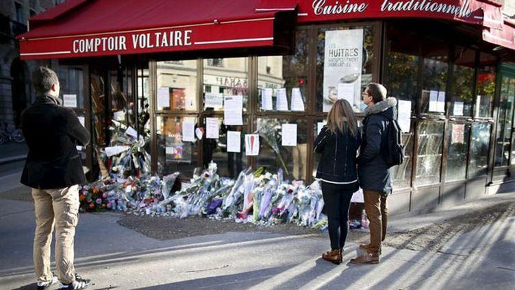 (Des passants se recueillent le 21 novembre devant l'un des sites des attentats du 13 novembre à Paris, qui ont fait 130 morts © REUTERS/Charles Platiau)