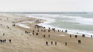 Malgré le vent, des promeneurs profitent des températures agréables sur laplage deScheveningen, aux Pays-Bas, le 26 décembre. (MAXPPP)