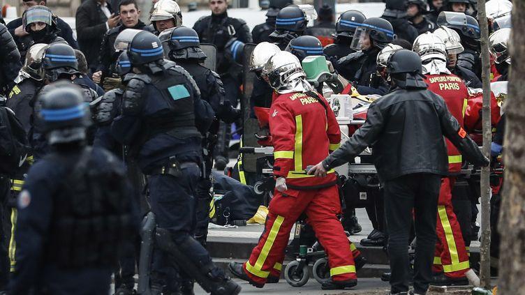 Les pompiers évacuent le policier victime d'un malaise cardiaque place de la République à Paris, le 23 mars 2019. (ZAKARIA ABDELKAFI / AFP)