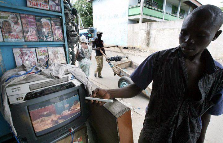 Un homme lançant un film Nollywood dans les rues d'Abidjan (16 juin 2007). (KAMBOU SIA / AFP)