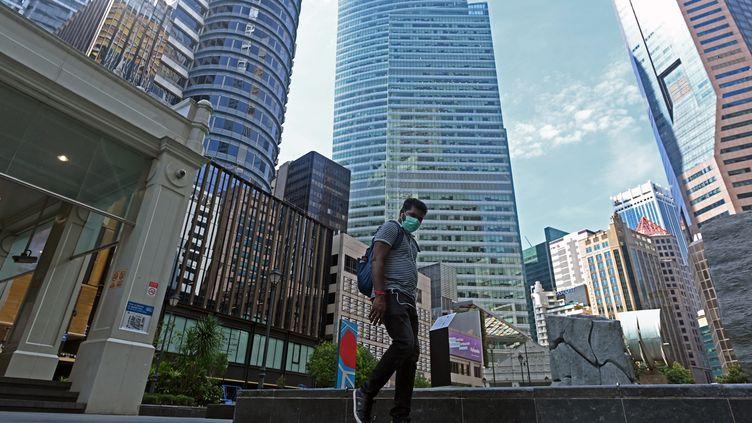 Un homme portant un masque de protection marche dans les rues de Singapour, le 14 avril 2020. (ROSLAN RAHMAN / AFP)