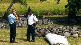 Un policier et un gendarme se tiennent devant le flaperon d'avion retrouvé à Saint-André, àLa Réunion, le 29 juillet 2015. (YANNICK PITOU / AFP)