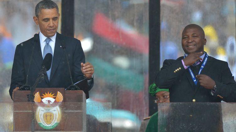 Thamsanqa Jantjie au côté de Barack Obama lors de la cérémonie d'hommage à Nelson Mandela, le 10 décembre 2013 à Johannesburg. (ALEXANDER JOE / AFP)
