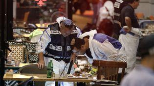 Des policiers israéliens inspectent un restaurant, après une attaque armée qui a fait trois morts, à Tel Aviv, le 8 juin 2016. (JACK GUEZ / AFP)