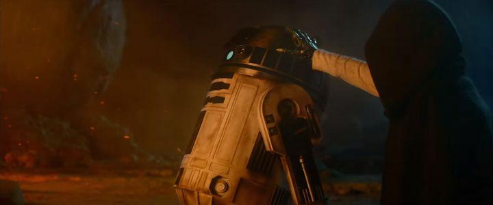 Le fameux R2-D2 et un mystérieux personnage caché sous une capuche, qui pourrait bien être Luke Skywalker. (STAR WARS / YOUTUBE)