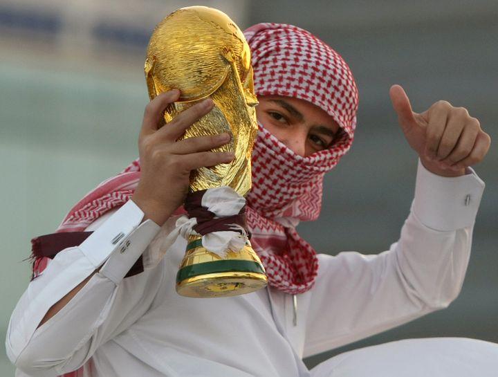 Un Qatari brandit une reproduction de la Coupe du monde de football, à Doha, le 3 décembre 2010. (MARWAN NAAMANI / AFP)