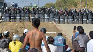 Les forces de l'ordre font face aux manifestants qui protestent contre le coup d'Etat, à Naypyidaw (Birmanie), le 15 février 2021. (STR / AFP)