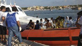 Des migrants arrivent à Lampedusa (Italie) à bord d'un bateau des garde-côtes italiens, le 3 octobre 2013, après le naufrage de leur embarcation, dans lequel ont péri des dizaines de personnes. (NINO RANDAZZO / REUTERS)