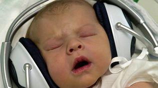 Un bébé écoute de la musique dans une maternité de Bratislava (Slovaquie), le 6 août 2004. (MAXPPP)
