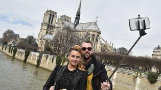 Des touristes utilisent une perche à selfie pour immortaliser leur passage à Paris, le 7 mars 2015. (DOMINIQUE FAGET / AFP)