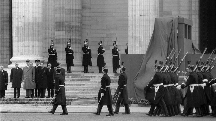 Le général de Gaulle entouré de Georges Pompidou (à sa gauche), d'André Malraux (à sa droite), et de nombreuses personnalités rendent un dernier hommage à Jean Moulin lors du transfert de ses cendres au Panthéon, à Paris, le 19 décembre 1964. (AFP)