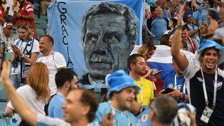"""Les supporters uruguayens brandissent un portrait du sélectionneur Oscar Tabarez, lors du 8e de finale remporté par la """"Celeste"""" contre le Portugal, à Sotchi (Russie), le 30 juin 2018. (ALEXANDR KRYAZHEV / SPUTNIK / AFP)"""
