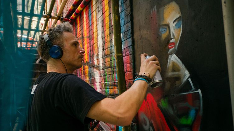 Le street artist Dan Kitchener peint à la bombe devant un bar de Hong Kong.  (Anthony Wallace / AFP)