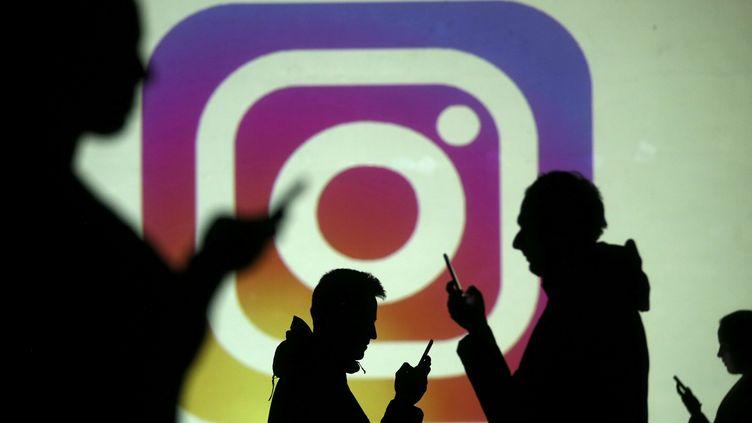 Des utilisateurs de smartphones photographiés près du logo vidéoprojeté d'Instagram le 28 mars 2018 en Bosnie-Herzégovine. (DADO RUVIC / REUTERS)