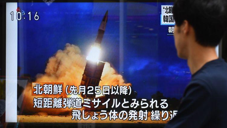 """Un passant devant un journal télévisé évoquant ce nouveau tir de """"projectiles non-identifié"""", à Tokyo, le 16 août 2019. (KAZUHIRO NOGI / AFP)"""