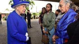 La reine Elisabeth II rencontre les familles touchée par l'incendie d'une tour de logements sociaux à Londres dans un centre sportif qui leur sert provisoirement d'abri, le 16 juin 2017 à Londres (Royaume-Uni). (DOMINIC LIPINSKI / POOL)