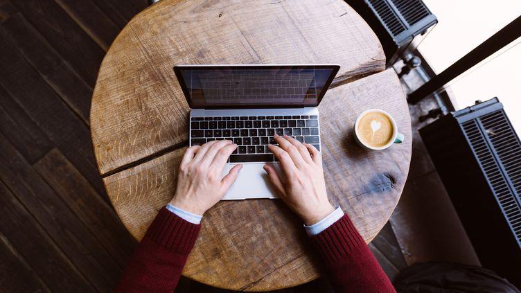 Image d'illustration d'un homme écrivant sur son ordinateur dans un café (mars 2019) (ALEXANDER SPATARI / MOMENT RF / GETTY)