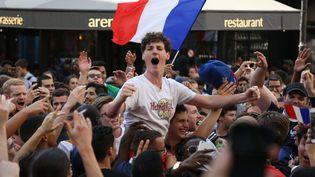 Des supporters fêtent la victoire des Bleus face à l'Uruguay (2 à 0) en Coupe du monde, à Paris, le 6 juillet. (ZAKARIA ABDELKAFI / AFP)