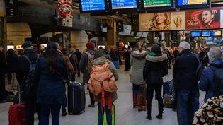 Des voyageurs se renseignent sur le trafic des trains, le 18 décembre 2019, à la gare Montparnasse, à Paris. (ESTELLE RUIZ / NURPHOTO / AFP)
