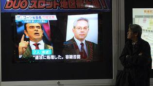 Un programme de télévision montrant Carlos Ghosn (à gauche) et Greg Kelly, le 30 novembre 2018 à Tokyo (Japon). (KAZUHIRO NOGI / AFP)
