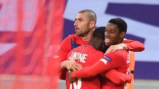 L'attaquant lillois Burak Yilmaz félicité par ses coéquipiers après avoir marqué un but lors du match de LigueEuropa entre le LOSC et le Sparta Prague au stade Pierre-Mauroy de Villeneuve-d'Ascq(Nord), le 3 décembre 2020. (DENIS CHARLET / AFP)