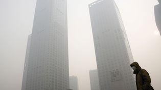 Un homme porte un masque en raison de la pollution dans le quartier financier de Pékin (Chine), le 30 novembre 2015. (KIM KYUNG HOON / REUTERS)