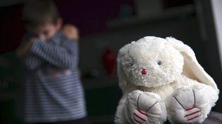 Un enfant prostré et une peluche. Photo d'illustration. (LIONEL VADAM / MAXPPP)