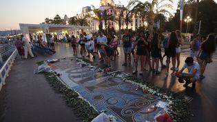 Des personnes se recueillent sur la promenade des Anglais, le 14 juillet 2017,en mémoire des victimes de l'attentat de Nice (Alpes-Maritimes). (VALERY HACHE / AFP)
