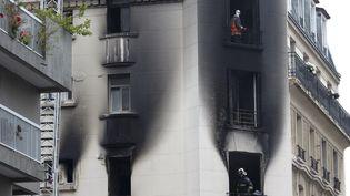 Des pompiers inspectent un immeuble touché par un incendie, le 6 septembre 2014, à Paris. (KENZO TRIBOUILLARD / AFP)
