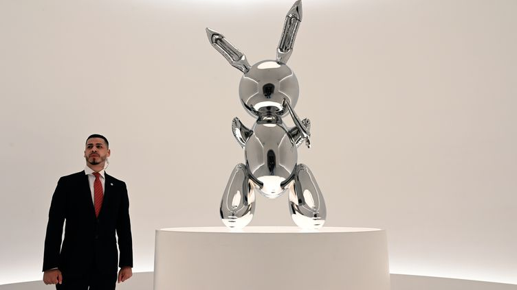 """Un agent de sécurité se tient devant le """"Rabbit"""" (Lapin) de l'artiste américain, Jeff Koons, le 3 mai 2019, à New York. (TIMOTHY A. CLARY / AFP)"""