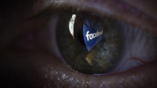 Le logo Facebook qui se reflète dans un œil. (THOMAS TRUTSCHEL / PHOTOTHEK)