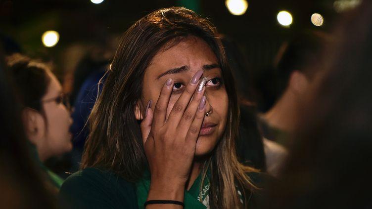 Une jeune femme venue militer pour la dépénalisation partielle de l'avortement, à Quito (Equateur), à l'annonce du votre contre le projet de loi, le 17 septembre 2019. (RODRIGO BUENDIA / AFP)