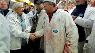 La candidate du Front national à l'élection présidentielle Marine Le Pen serre les mains d'un boucher en visitant le pavillon de la viande, au marché de Rungis (Val-de-Marne), le 25 avril 2017. (CHARLES PLATIAU / POOL)