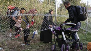 Des migrants passent sous la clôture de sécurité d'une autoroute, près du village de Horgos, en Serbie,à la recherche d'un point d'entrée vers la Hongrie, qui a fermé sa frontière, le 14 septembre 2015. ( MARKO DJURICA / REUTERS)