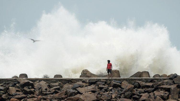 Un homme passe devant le port de pêche de Kasimedu à Chennai (Inde), le 19 mai 2020, alors que le cyclone Amphan se dirige vers la côte est du pays. (ARUN SANKAR / AFP)
