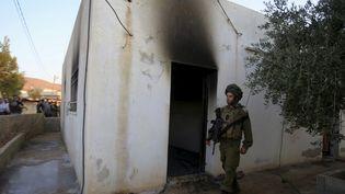 Un soldat israélien monte la garde devant lamaison incendiée,dans le village de Doma, près de Naplouse (Cisjordanie), le 31 juillet 2015. (ABED OMAR QUSINI / REUTERS)