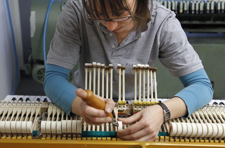 Une employée de la manufacture Pleyel travaille sur un piano à l'atelier de fabrication de Saint-Denis (Seine-Saint-Denis), le 3 décembre 2010. (FRANCOIS GUILLOT / AFP)